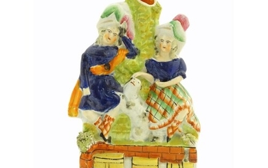 A Victorian Staffordshire pottery bud vase with two children...