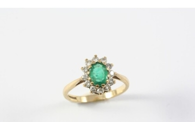 AN EMERALD AND DIAMOND CLUSTER RING the oval-shaped emerald ...