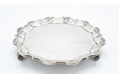 A hallmarked silver salver with shaped edge raised on three ...