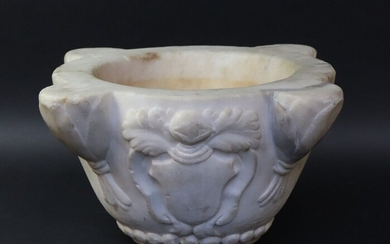 White marble mortar with four ribs in foliage sheaths. The body is decorated with an escutcheon topped by a helmet. Frieze of pearls on the base. 18TH, 19TH CENTURY. Height 16 cm. Max. diameter 33,5 cm