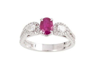 A DIAMOND AND RUBY DRESS RING, the oval ruby flanked by pear...