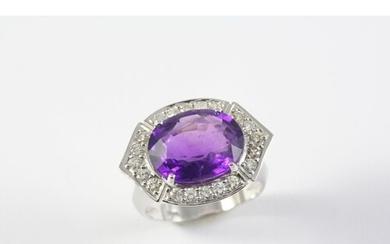 AN AMETHYST AND DIAMOND CLUSTER RING the oval-shaped amethys...