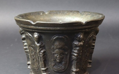 Bronze mortar with six ribs in the form of caryatids interspersed with six medallions of a face topped with a feather. Lyon or Puy en Velay. 17th century. Height 9,8 cm. Diameter 14.3 cm. Six notches cut in the upper edge
