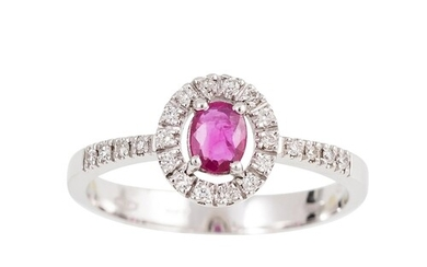 A DIAMOND AND RUBY CLUSTER RING, the oval ruby to a brillian...