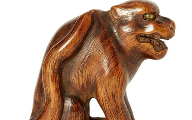 A Japanese wood netsuke, 19th century, carved as a growling dog with inlaid eyes, 4cm