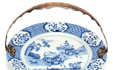 A blue and white plate with silver handle
