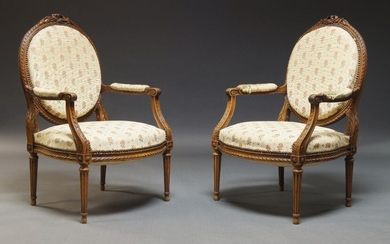A pair of Louis XVI style fauteuils, first half 20th Century, the oval backs surmount with carved ribbon and foliate decoration, upholstered in floral pattern fabric, on tapering fluted legs with ovoid feet (2)