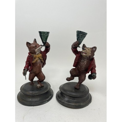 A pair of painted bronze candlesticks, in the form of a fox ...