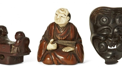 Three Japanese wood netsuke, 19th century, carved as Hotei and Karako playing Go; an Okina Noh mask; and seated nobleman with metal fan, hands and head of ivory, largest 4cm (3)