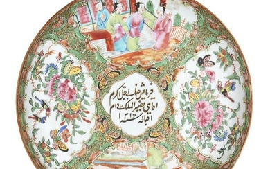 A Chinese Canton export porcelain dish for the Islamic market, late 19th century, painted in famille rose enamels with panels of figures in conversation and birds and butterflies amongst flowering peony blossoms, the central panel painted with an...