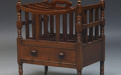 A Victorian mahogany Canterbury, with four divisions and pierced handle, having drawer to base, on turned legs with brass caps and castors, 59cm high, 47cm wide, 35.5cm deep