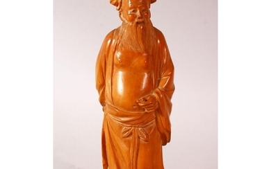 A CHINESE CARVED HARD WOOD FIGURE OF AN IMMORTAL - the figur...