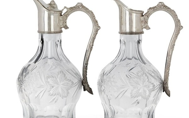 A pair of silver mounted cut glass wine ewers, Sheffield, c.1995, CJ Vander, one ewer lacking cover to lid, both designed with stylised branch handles, the bulbous glass bodies cut and etched with foliate designs, 25.5cm high (2) Note: The Athenæum...