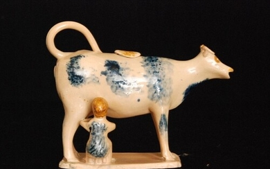 An early 19th Century cow creamer and cover with milk maid a...