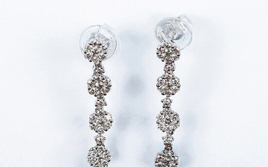 Beautiful long white gold earrings, cascading rosettes set with...