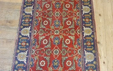 A Persian red ground rug, with main blue border, centre with...