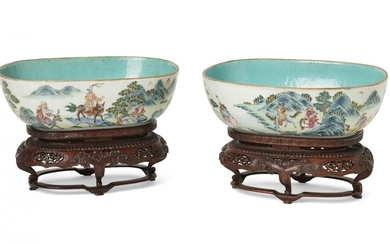 A pair of Chinese porcelain oval bowls, Jiaqing period, each painted to the exterior with 'tribute bearers' in a mountainous landscape, interior and base covered with a turquoise glaze, 25.5cm wide, on carved hardwood stands (2) Note: The foreign...