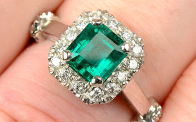 A platinum emerald and diamond cluster ring.
