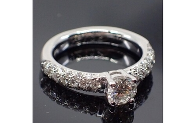 An 18ct gold diamond solitaire ring set with diamond shoulde...