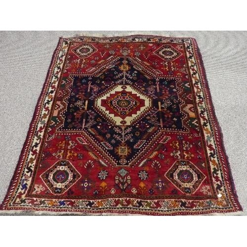 Tribal rugs; a Persian Qashqai red and blue ground rug, the ...