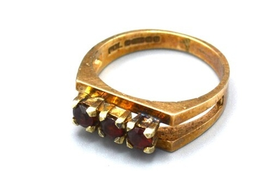 A 9ct Yellow Gold Dress Ring set with three garnets within a...