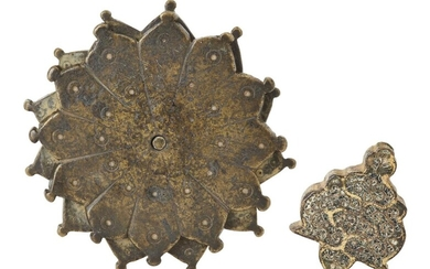 A gilt metal hilt with filigree decoration and a rotating bronze flower, India, 19th century or earlier, the hilt with a dense pattern of scroll work, opening to bottom presumably for a blade and to the top for a finial; the flower formed of two...