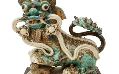 A large Chinese pottery figure of a Buddhist lion, late Ming dynasty, modelled seated, with back glazed in tones of turquoise and yellow, 36cm high
