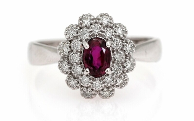 A ruby and diamond ring set with an oval-cut ruby encircled by numerous diamonds, mounted...