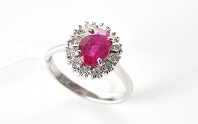 A RUBY AND DIAMOND CLUSTER RING IN 18CT WHITE GOLD, THE OVAL CUT RUBY ESTIMATED 1.55CTS, SIZE L, 3.5GMS