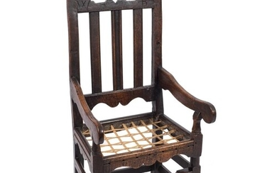 A late 17th Century oak open armchair:, the back with shaped...