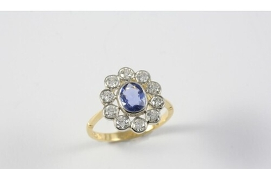 A SAPPHIRE AND DIAMOND CLUSTER RING the oval-shaped sapphire...