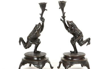 A pair of Japanese bronze frog form candlesticks