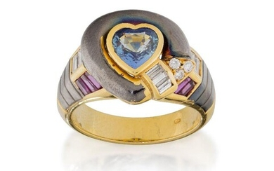 A sapphire, ruby and diamond ring, the central heart shaped sapphire collet within a black oxidised surround with brilliant and baguette-cut diamond detail, to baguette-cut diamond and ruby triple row shoulders with black oxidised reeded panel...