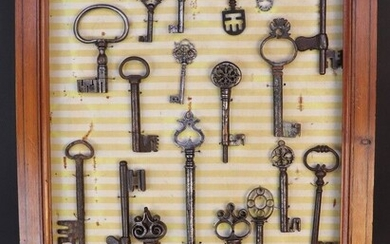 Panel of twenty four keys from the XIVth to the XIXth century. Restorations to some. A small hand vise is attached.