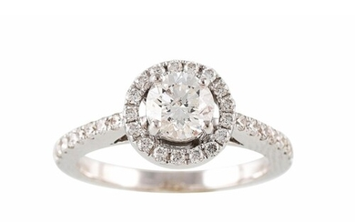 A DIAMOND HALO CLUSTER RING, with diamond shoulders, mounted...