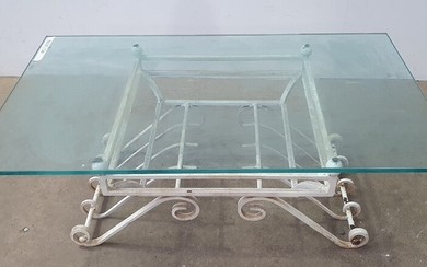 A WROUGHT IRON BASED GLASS TOP COFFEE TABLE