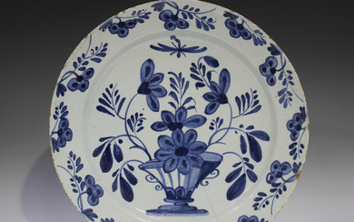 An English Delft charger, 18th century, painted in blue with a vase and flowers, the rim similarly d