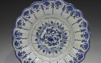 A Delft moulded dish, 18th century, painted in blue with flowers, the fluted rim with a continuous s