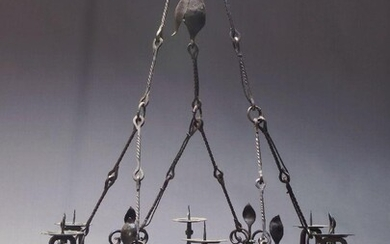 A large French wrought iron six light ceiling light, of circular form with six candles sconces and six light fittings, with Fleur de Lys and floral wrought metal motifs, approx. 135cm high, 89cm diameter