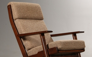 Hans J. Wegner. High-backed lounge chair with a...
