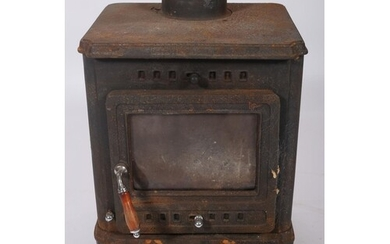 A CAST IRON FREE STANDING SOLID FUEL STOVE on moulded legs 6...