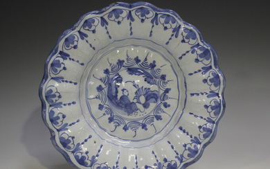 A Delft moulded dish, 18th century, painted in blue with a chinoiserie style figure within a landsca