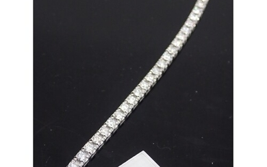 A diamond tennis bracelet set in 18ct gold with HRD Certific...