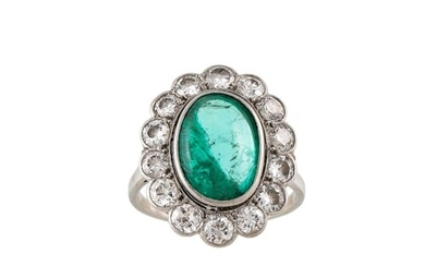 AN EMERALD AND DIAMOND CLUSTER RING, the oval cabochon emera...