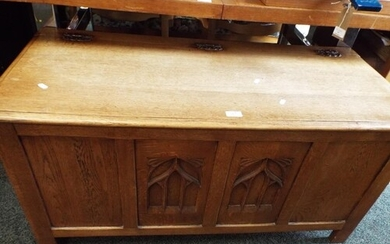 An oak coffer with arch window carved panels