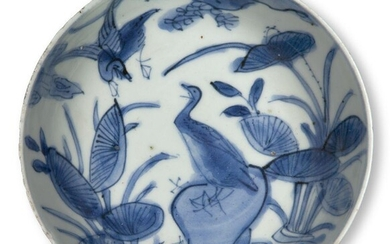 A Chinese porcelain blue and white kosometsuke dish, Tianqi period, painted with a bird perched atop a rocky outcrop with large lotus blooms emerging from the surrounding water, 13.5cm diameter Provenance: with paper collection label to base that...