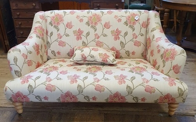 A modern sofa, in floral cream ground fabric, on turned legs...